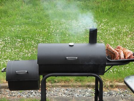 Charcoa offsetl smoker during bsackyard cookout