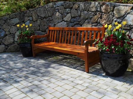 Garden bench surrounded byflowerpots with spring vegetation
