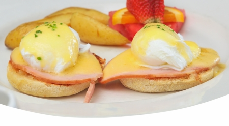 Breakfast plate with eggs Benedict, fries and fruit Stock Photo