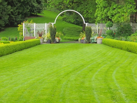 Outdorr wedding place in the garden, with grass lawn and white arc Editorial