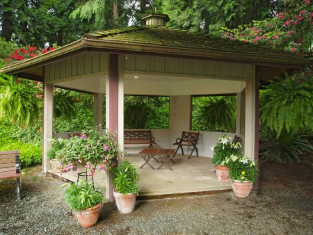 gazebo: Woodent gazebo with roof covered with moss in the garden Editorial