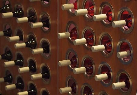 Bottles of wine stored in a wooden wine rack photo