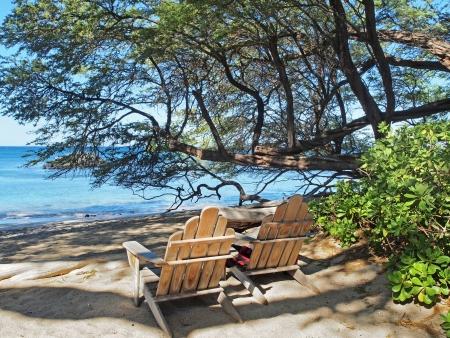 adirondack chair: Two wooden Adirondack  chairs overlooking sandy ocean beach