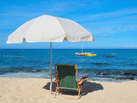 Beach chair with ambrella on the ocean shore, overlooking the ocean