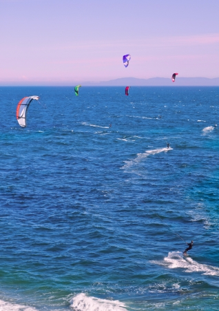 boarders: A few kite boarders surfing the coastal waters at the sunset time