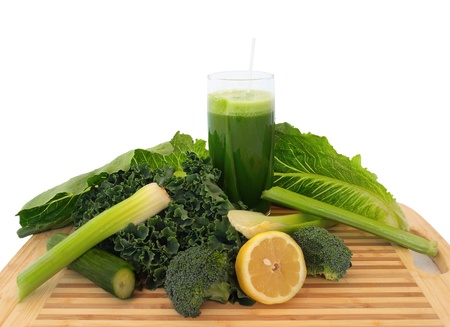 Glass of green vegetable juice with fresh vegeatbles on a cutting board, over white