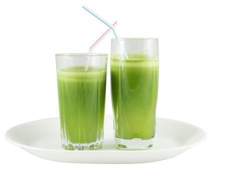 Two glasses with green vegetable juice on a plate against white