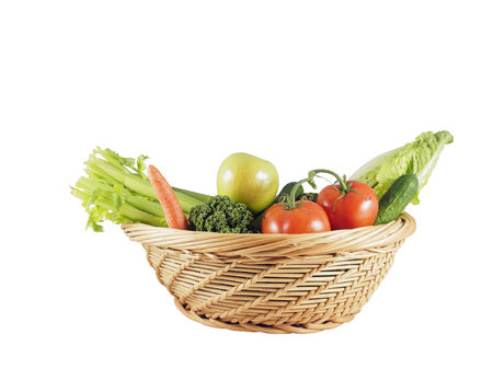 Basket with fresh vegetables against white background photo