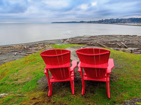 adirondack chair: Two red Adirondack chairs overlooking the ocean shore Stock Photo
