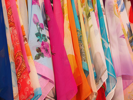 tela algodon: Bufandas coloridas que cuelgan en una fila en el mercado de la calle del verano Foto de archivo