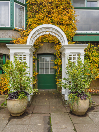 Entrance door with arc decorated with ivy in autumn colors Stock Photo