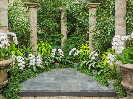 Ceremonial portal with stone columns and white orchids