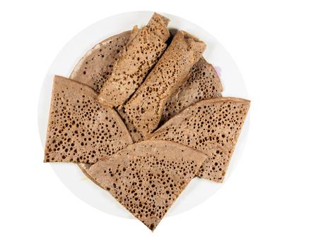 Traditionele Ethiopische flatbread van gefermenteerde teffbloem op een witte plaat, gesneden en opgerold