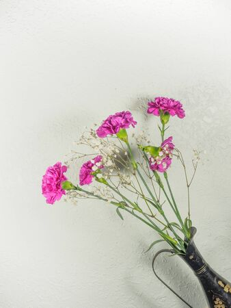 Bouquet of carnations with shadow on the grungy wall