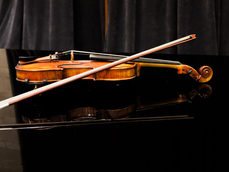 Violin on the grand piano in a concert hall, close-up Stock Photo