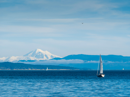 View on Mt. Baker from Vancouver Island, Canada, with sailboats cruising the ocean