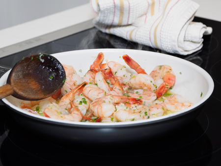 Cooking shrimp scampi in a white pan on black ceramic stove