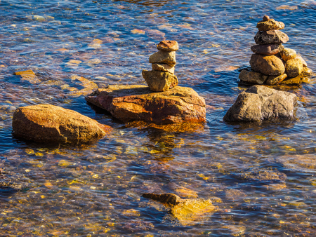 Stack of rocks balanced in a pyramid form in ocean water near the shore