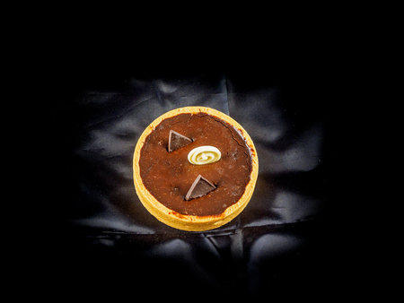 Dessert of freshly baked tarts with chocolate filling on black background