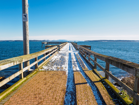 Public fishing pier in Sidney, British Columbia, Vancouver Island, Canada, covered in snow as a rare occasion. Mount Baker in the background