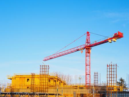 Construction crane on a building site against blue sky background