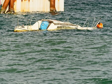Sunken boat in the coastal waters, waiting for the towing to the shore 版權商用圖片 - 128448330