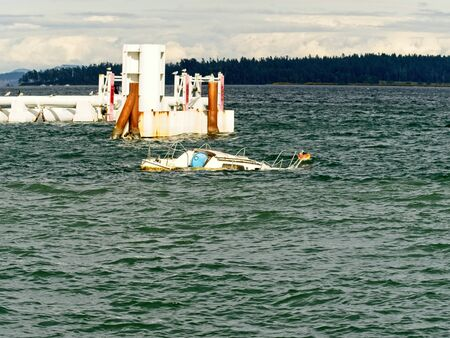 Sunken boat in the coastal waters, waiting for the towing to the shore