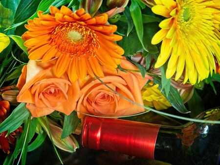 Bouquet of flowers and bottle of wine arranged on black surface