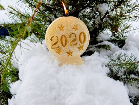 Christmas themed background with snow, fir tree and lit candle inscribed with 2020. Room for text