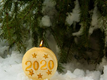Christmas themed background with snow and lit candles inscribed with 2020. Room for text Banco de Imagens