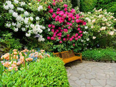 Bank im üppigen Frühlingsgarten mit Gehwegen zwischen Blumenbeeten Standard-Bild