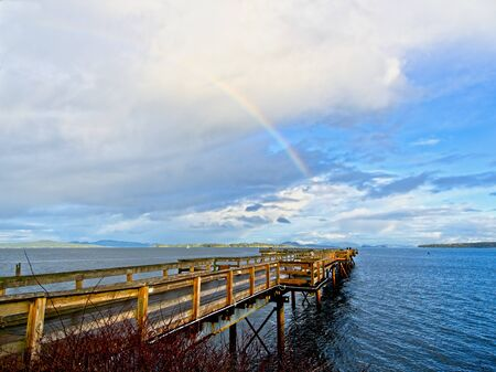 Rainbow during rain season over fishing pier in Sidney BC, Vancouver Island Imagens