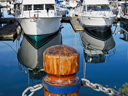 Wooden posts with chain links decorate the perimeter of Sidney marina with moored yachts Stok Fotoğraf