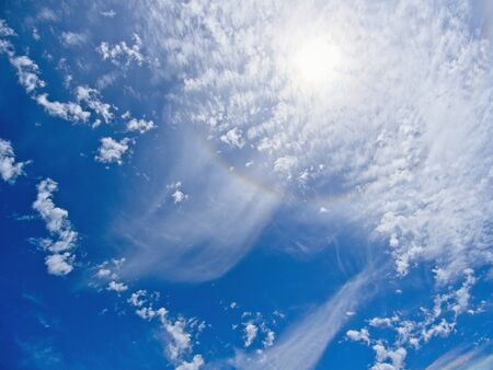 Deep blue sky with fanciful cloud formations and rainbow halo around the sun 스톡 콘텐츠