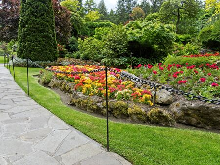 Paved walkway in the springtime garden among the lawns and flower beds