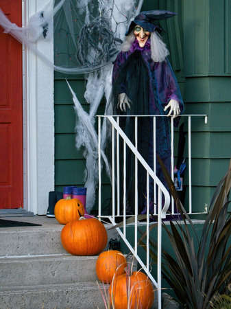 Full-size witch doll stands at the porch of the house as a halloween decoration. Pumpkins decorate the steps