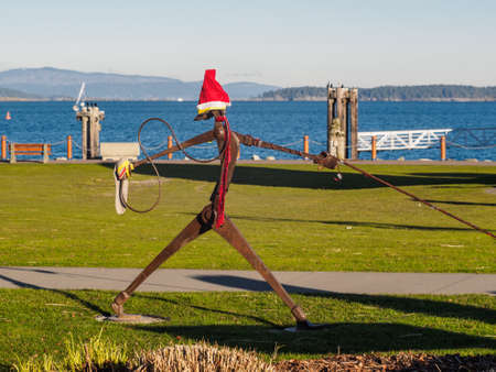 Sidney, BC Canada - January 1, 2019. Sculpture at the lawn in Sidney, decorated with red hat and scarf for Christmas and New year celebration 新聞圖片