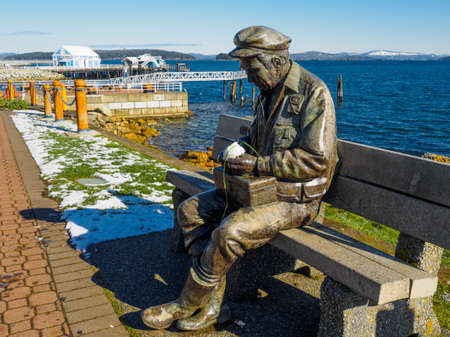 Sidney, BC Canada - February 2, 2018. Sculpture Old Man by the Sea at the fishing pier in Sidney, with snowball on a rare snowy day