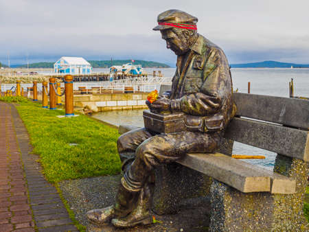 Sidney, BC Canada - October 16, 2018. Sculpture Old Man by the Sea at the fishing pier in Sidney, decorated for Thanksgiving