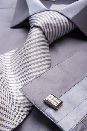 Close up photo of a folded grey shirt with a striped tie 版權商用圖片