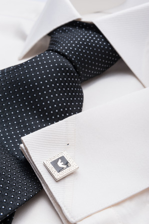men shirt: Close up photo of a folded formal white men shirt with a black tie