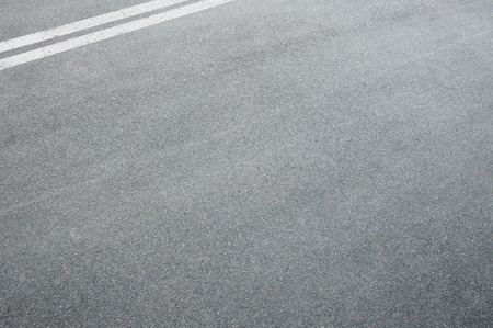 Horizontal shot of an asphalt on the highway road with dividing lines at the top corner