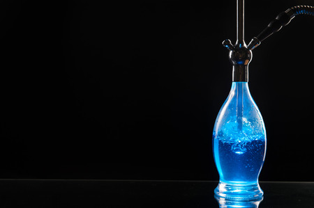 Hookah, shisha or waterpipe with blue glow on a black background shot in a studio