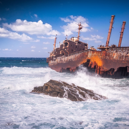 andros: Parts of the abandoned, covered in rust shipwreck on Andros island in Greece