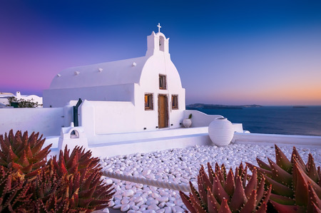 Greece: White othodox church in Oia on Santorini, Greece, during a sunset with red plants in front