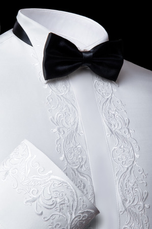 fancywork: Vertical studio shot of a formal white shirt with fancywork and a black bowtie on black background Stock Photo