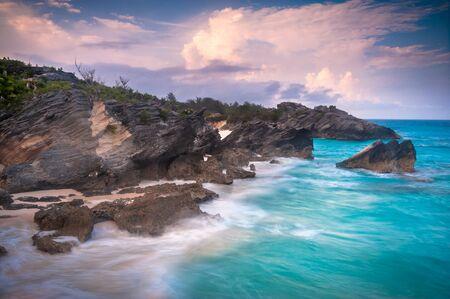 절벽을 때리는 아름 다운 tuquoise 파도와 버뮤다 섬에 호스 슈 베이 해변 위로 일몰보기