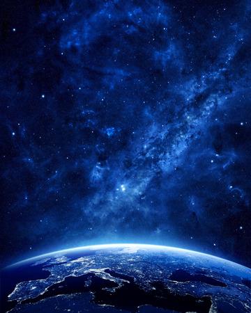 wereldbol: Aarde bij nacht gezien vanuit de ruimte met blauwe, gloeiende sfeer en ruimte aan de top. Perfect voor illustraties. Elementen van deze afbeelding geleverd door NASA Stockfoto