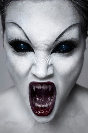 undead: Close up portrait of a screaming undead girl with sharp teeth, white skin and black eyes Stock Photo