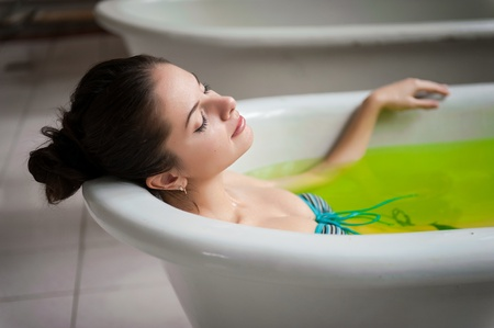 Wellness - young woman floating in Spa filled with water with pine tree and other herbs extracts Stock Photo